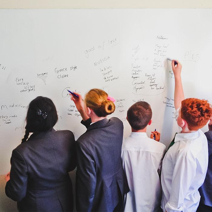 Studenti che utilizzano muri effetto lavagna scrivibili in classe muro pittato con smarter surfaces tinta cancellabile