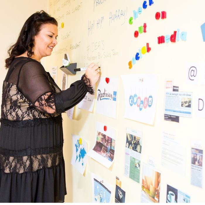 donna scrivendo con pennarello su muro magnetico lavagna