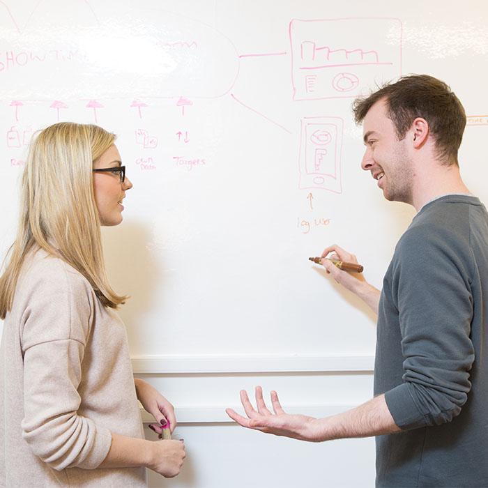 Uomo che disegna sul muro dell ufficio realizzato con carta da parati effetto lavagna bianca durante una riunione