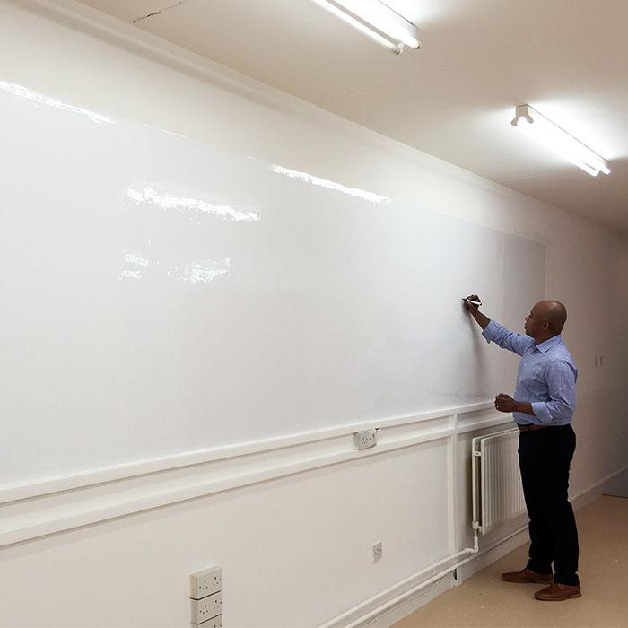 uomo che scrive con pennarello su superficie brillante creata con carta da parati effetto lavagna smart