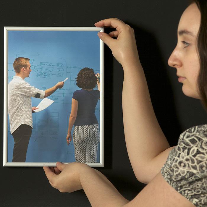 Donna che appende una cornice con foto grazie a vernice effetto super magnetico smart sul muro