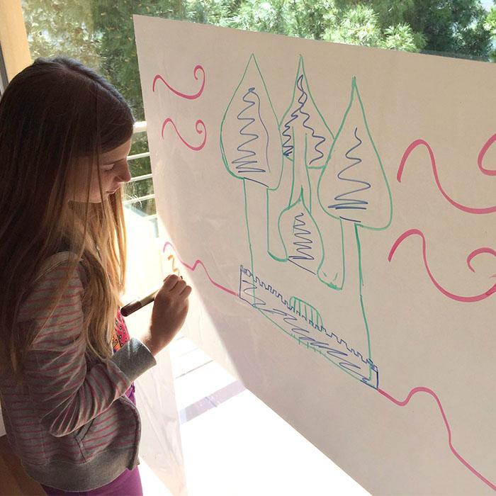 bambina che disegna su un foglio scrivibile smart
